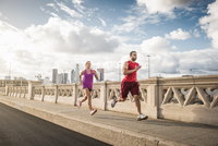 Male and female runners running across bridge, Los Angeles, California, USA