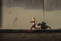 Female runner running on sidewalk