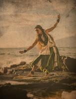 Enhanced image of woman hula dancing on coastal rocks wearing traditional costume, Maui, Hawaii, USA