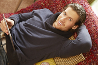 Overhead portrait of young man reclining on sofa