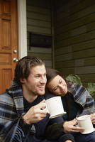 Young couple sitting on porch step wrapped in blanket