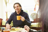 Over shoulder view of young man drinking coffee at breakfast table
