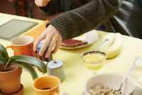 Cropped shot of young womans hands holding jam jar at breakfast table