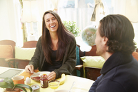 Young couple laughing at breakfast table