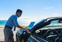 Young businessman at coast parking lot typing on laptop on car hood