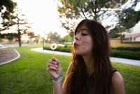 Young woman blowing dandelion clock in park 11015258382| 写真素材・ストックフォト・画像・イラスト素材|アマナイメージズ
