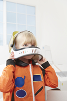 Young girl playing dress up, wearing astronaut outfit