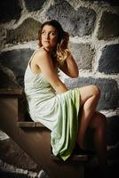 Young woman wearing dress sitting on stairs 11015258579| 写真素材・ストックフォト・画像・イラスト素材|アマナイメージズ