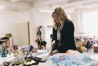 Female textile designer cutting textiles in design studio