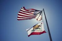 American and Californian flags against blue sky, California, USA