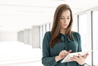 Young businesswoman using digital tablet in empty new office