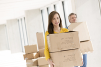 Businessman and businesswoman carrying cardboard boxes in empty new office
