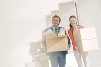 Businessman and businesswoman carrying cardboard boxes in new office