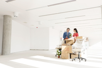 Businesswoman and man unpacking cardboard boxes  in new office