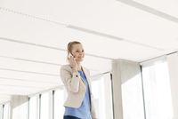 Businesswoman chatting on smartphone in new office