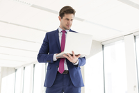 Young businessman using laptop in new office