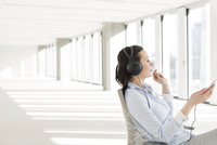 Businesswoman listening to headphones in empty new office
