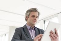 Mature businessman using digital tablet in office