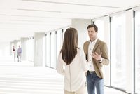 Young businessman and woman chatting in office corridor