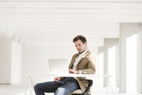 Businessman using laptop in empty new office
