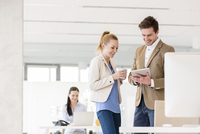 Young businessman and woman using digital tablet in office