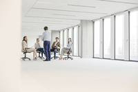 Businessman talking to team in empty new office