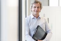 Portrait of mature businessman holding workbook in office
