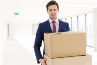 Portrait of businessman carrying cardboard boxes in new office
