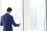 Businessman looking at blueprint in new office