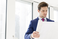Young businessman looking at blueprint in new office