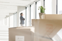Mature businessman in new office looking out of window