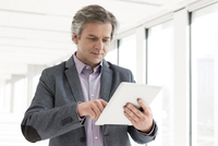 Mature businessman in new office using digital tablet