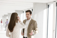 Businessman and woman chatting in office corridor