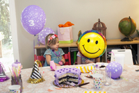 Two girls sitting at birthday party table with cake playing with smiley face balloon