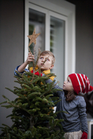 Portrait of a boy and girl putting star decoration on top of christmas tree