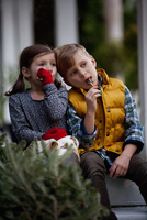 Portrait of a boy and girl eating festive candy canes