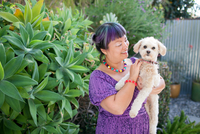 Mid adult woman outdoors, holding dog