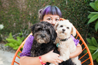 Mid adult woman sitting outdoors, hugging two dogs