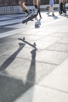 Skateboarder performing trick, low section