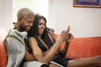 Young male couple on sofa, looking at smartphone
