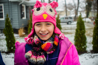 Portrait of girl wearing pink hat with face in snowy garden