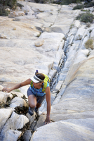Young female rock climber climbing up crevice,  Mount Wilson, Nevada, USA