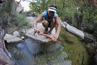 Female hiker rinsing clothes in rock pool, Mount Wilson, Nevada, USA