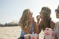 Three young women, sitting on beach, eating popcorn