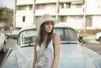Portrait of young woman leaning on car bonnet