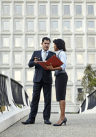 Business people standing talking holding red file and smartphone