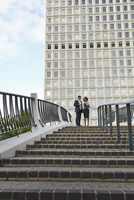 Low angle view of business people standing at top of stairway, City Hall East, Los Angeles, California, USA