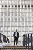 Business man standing at the top of stairway, wearing sunglasses, hands in pockets, looking away