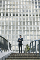 Low angle view of business man standing at top of stairway looking at watch
