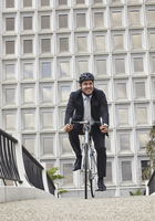 Front view of mid adult business man riding bicycle, wearing helmet, smiling